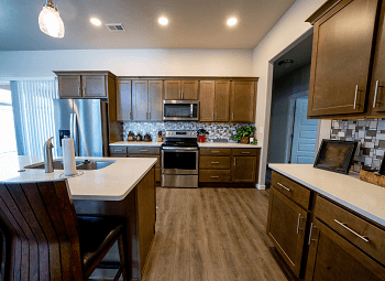 a kitchen with dark wood cabinets and an island